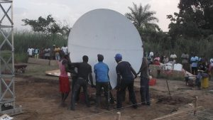 Fixing the VSAT antenna on support/pole with the locally hired technicians